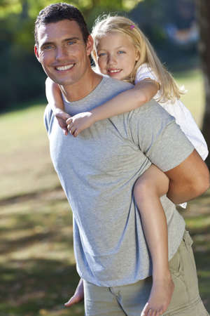 single parent: A young father with his blond daughter on his shoulders having fun in a sun bathed green park