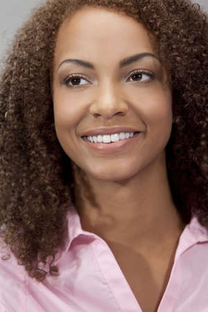 A beautiful mixed race African American girl laying down with perfect teeth and smile Stock Photo