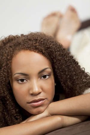 thoughtful woman: A beautiful mixed race African American girl laying down at home on a settee Stock Photo