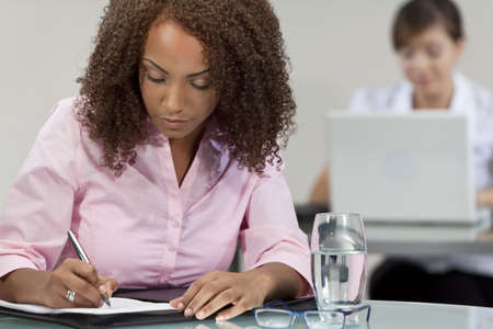A beautiful mixed race African American girl, student or businesswoman sitting at a desk and writing, behind her a chinese asian colleague is working on a laptop computer. Stock Photo - 5662084