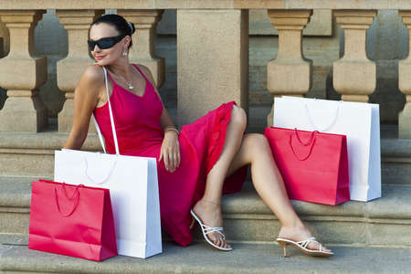 A classically beautiful latina woman in a red dress sitting with red and white shopping bags and looking happy photo