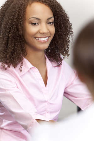 A beautiful mixed race African American young woman with perfect teeth and smile sitting and talking to a colleague out of focus in the foreground. Stock Photo - 5679433