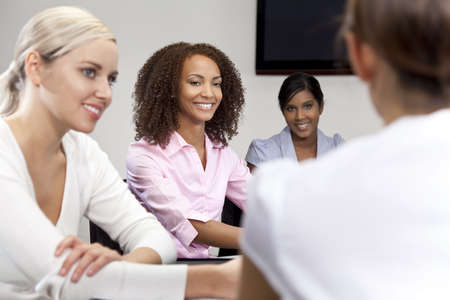 A smiling mixed race African American businesswoman and her three colleagues taking part in a happy business meeting, the focus is on the African American woman. photo