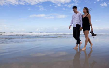 A beautiful romantic young man and woman couple walking hand in hand and barefoot on a beach. They are dressed as if it is after a night out and the girl is carrying her shoes. photo
