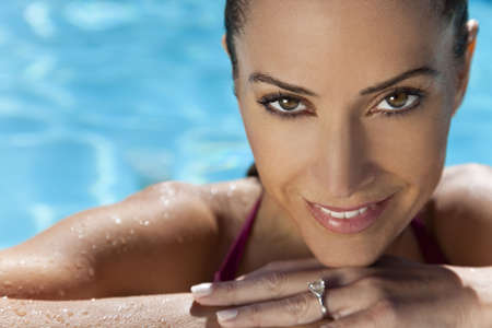 Close up portrait of a beautiful happy woman resting on her hands at the side of a sun bathed swimming pool Stock Photo - 5794994