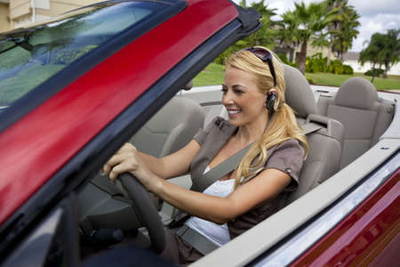 A beautiful young blond woman driving her convertible car and talking on her cell phone with a blurtooth headset photo