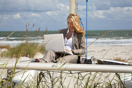 catamaran: A beautiful young woman in a smart suit sitting barefoot on the deck of a small catamaran sailing boat using her laptop computer with the beach and sea behind her