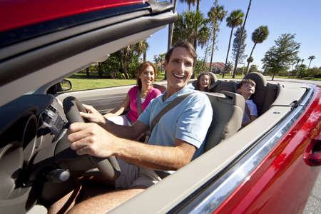 A family of four, mother, father, son and daughter driving in a convertible car on a sunny day in hot location with palm trees Stock Photo