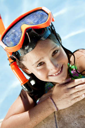 A happy young girl smiling and relaxing on the side of a swimming pool wearing orange goggles and snorkel Stock Photo - 5821234