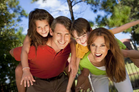 A modern family of father, mother, daughter and son playing together and having doing piggy back in a park Stock Photo - 5821244