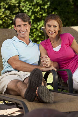 Portrait shot of an attractive, successful and happy middle aged man and woman couple in their thirties, sitting togther holding hands and smiling. photo