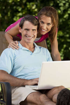 togther: Portrait shot of an attractive, successful and happy middle aged man and woman couple in their thirties, sitting togther outside using a laptop computer.
