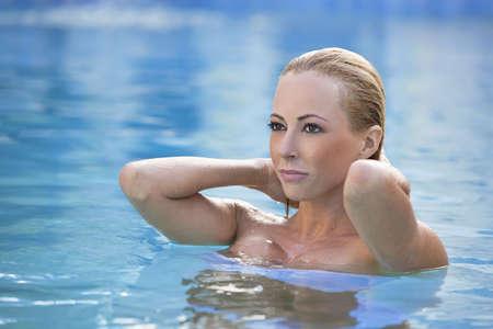 mujer ba�andose: Una bella mujer rubia de ba�o en una piscina azul en un ambiente de spa de belleza.