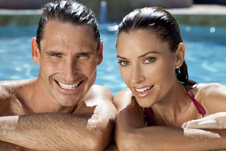 pool side: Close up portrait of a beautiful happy man and woman couple resting on their hands at the side of a sun bathed swimming pool smiling with perfect teeth.