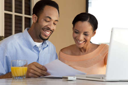 A happy African American man and woman couple in their thirties working on a laptop computer and looking at paperwork photo