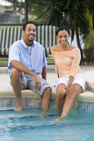 A happy African American man and woman couple in their thirties sitting wth their feet in a swimming pool photo