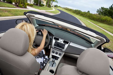 convertible: Rear view of a beautiful young blond woman driving her convertible car  Stock Photo