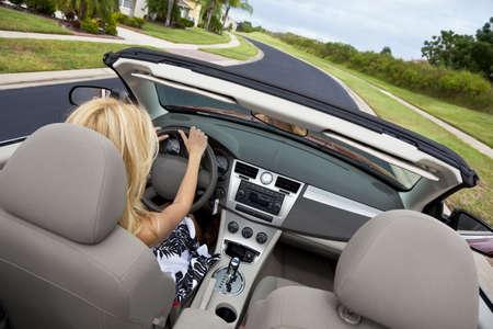 Vue arrière d'une belle jeune femme blonde au volant de sa voiture décapotable
