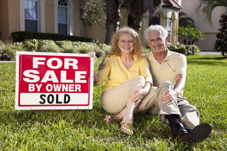 sold sign: Happy, smiling man and woman senior couple sitting on the grass outside their home with For Sale Sold by owner sign.