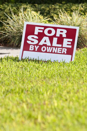property owners: House for sale by owner sign on the front lawn of a house