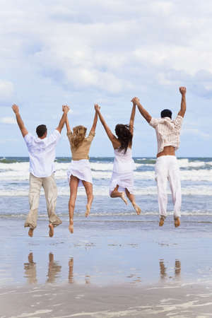 Four young people, two couples, holding hands, having fun and jumping in celebration on a beach Stock Photo - 5839636