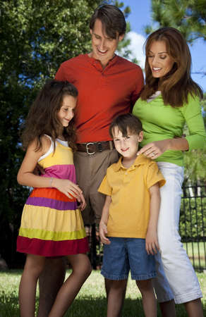 A modern family of father, mother, daughter and son playing together and having fun in a park. Stock Photo - 5839640