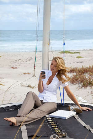 A beautiful young woman sitting barefoot on the deck of a small catamaran sailing boat using her smart phone to send a text with the beach and sea behind her photo