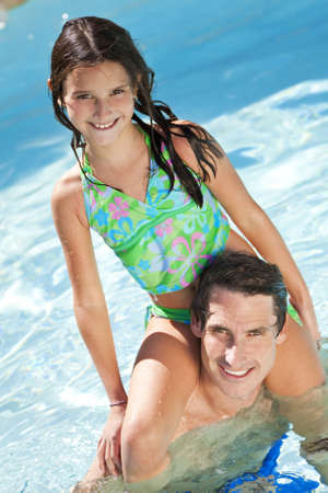 A father having fun with his daughter on his shoulders in a swimming pool Stock Photo