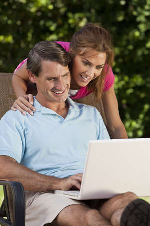 Portrait shot of an attractive, successful and happy middle aged man and woman couple in their thirties, sitting together outside using a laptop computer. photo