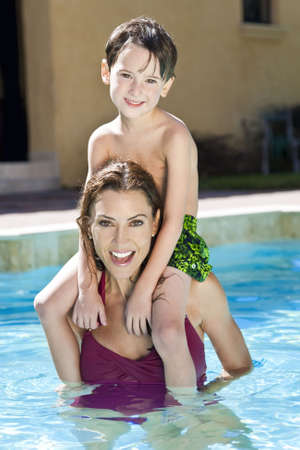 A mother having fun with her son on her shoulders in a swimming pool Stock Photo - 5858960
