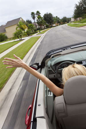 A beautiful young blond woman driving her convertible car with her hand in the air feeling the wind blowing photo