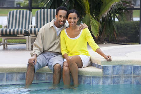 A happy African American man and woman couple in their thirties sitting with their feet in a swimming pool. photo