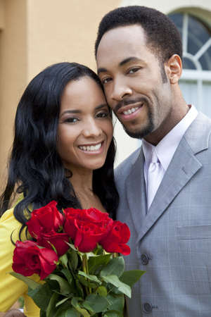 A romantic and happy African American man and woman couple in their thirties smiling together with a bunch of roses. photo