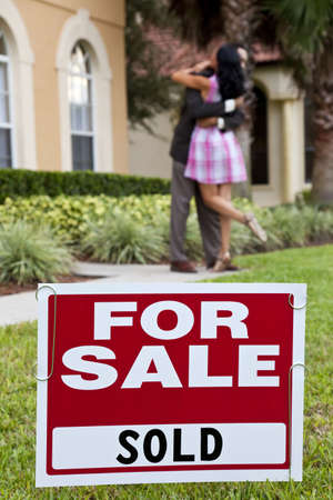 sold sign: House For Sale and Sold sign with African American couple celebrating the purchase of a house out of focus behind the sign.
