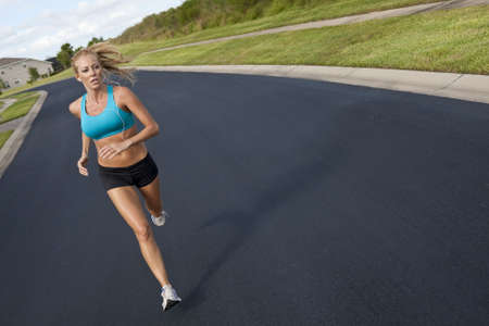 earphone: A beautiful fit and healthy blond woman road running while listening to music on her portable mp3 player