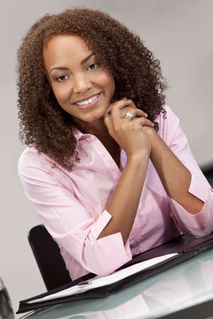 A beautiful mixed race African American girl, student or businesswoman sitting at a desk with a folder and pen. Stock Photo - 5944628