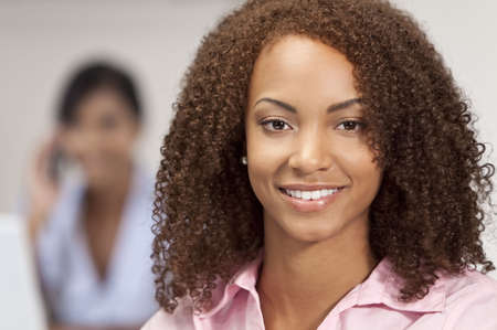 A beautiful mixed race African American girl with perfect teeth and smile behind her out of focus is an Asian girl talking on the phone