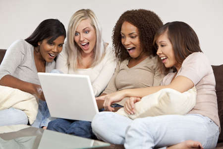 A group of four interracial beautiful young women having fun looking at something surprising and funny on their laptop computer and laughing Stock Photo - 5948157