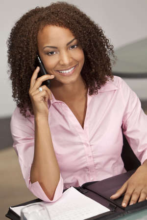 A beautiful mixed race African American girl, possibly a student or businesswoman sitting at a desk talking on her cell phone. Stock Photo - 5948155