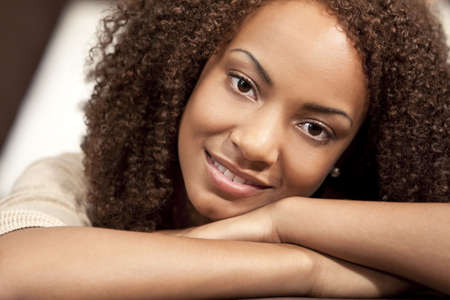 A beautiful mixed race African American girl laying down and resting on her hands Stock Photo - 5966556