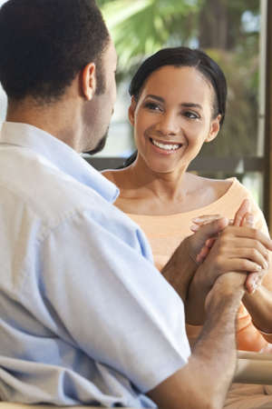 A happy African American man and woman couple sitting down and holding hands. Stock Photo - 5998948