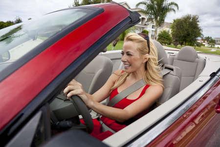 donna ricca: Una bella giovane donna bionda alla guida della sua auto convertibile indossa un vestito rosso e occhiali da sole