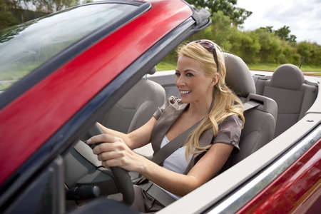 woman driving: A beautiful young blond woman driving her convertible car in the sunshine.