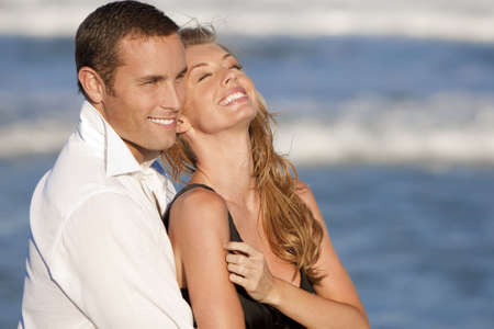 couple cuddling: A young man and woman embracing and laughing as a happy romantic couple on a beach