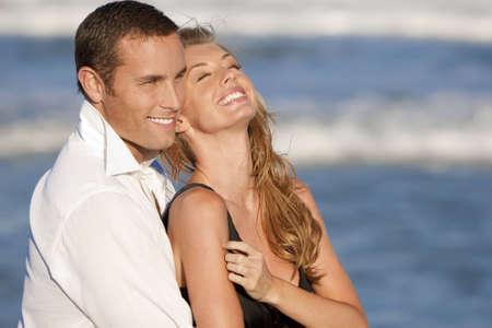 pareja abrazada: Un hombre joven y una mujer abraza y riendo como una feliz pareja rom�ntica en la playa  Foto de archivo