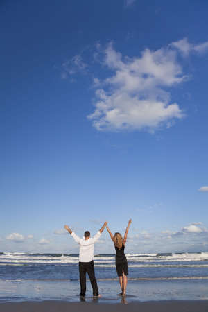 A young man and woman celebrating arms raised and holding hands as a romantic couple on a beach with a bright blue sky photo