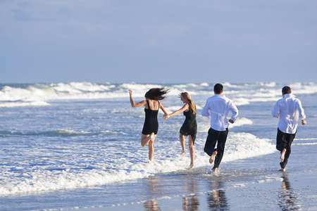Four young people, two couples, having fun and running into the sea on a beach Stock Photo - 6174976