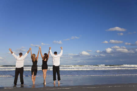 four hands: Four young people, two couples, holding hands, arms raised having fun and celebrating on a beach