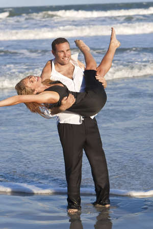 carrying girlfriend: A young man and woman couple having romantic fun in the sea on a warm sunny beach