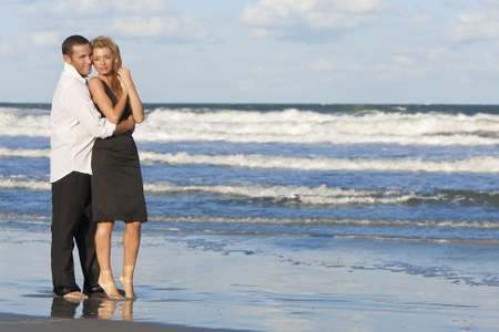 A young man and woman embracing as a romantic couple standing in the sea on a beach with a blue sky Stock Photo - 6180862